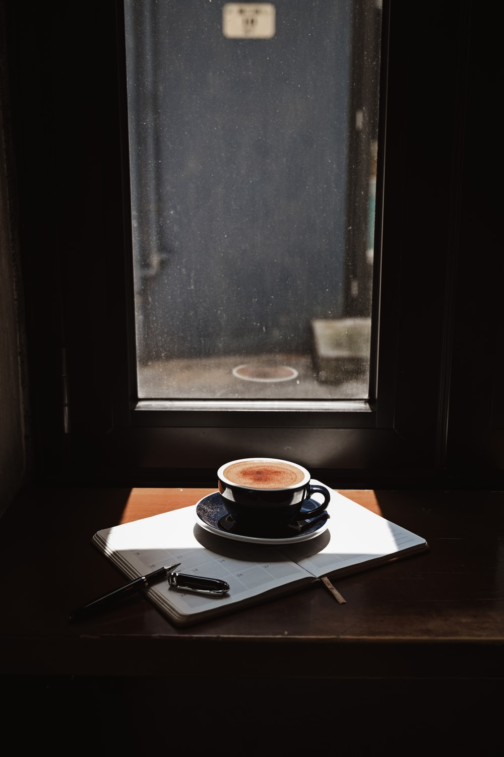 black and white ceramic teacup on saucer on brown wooden table