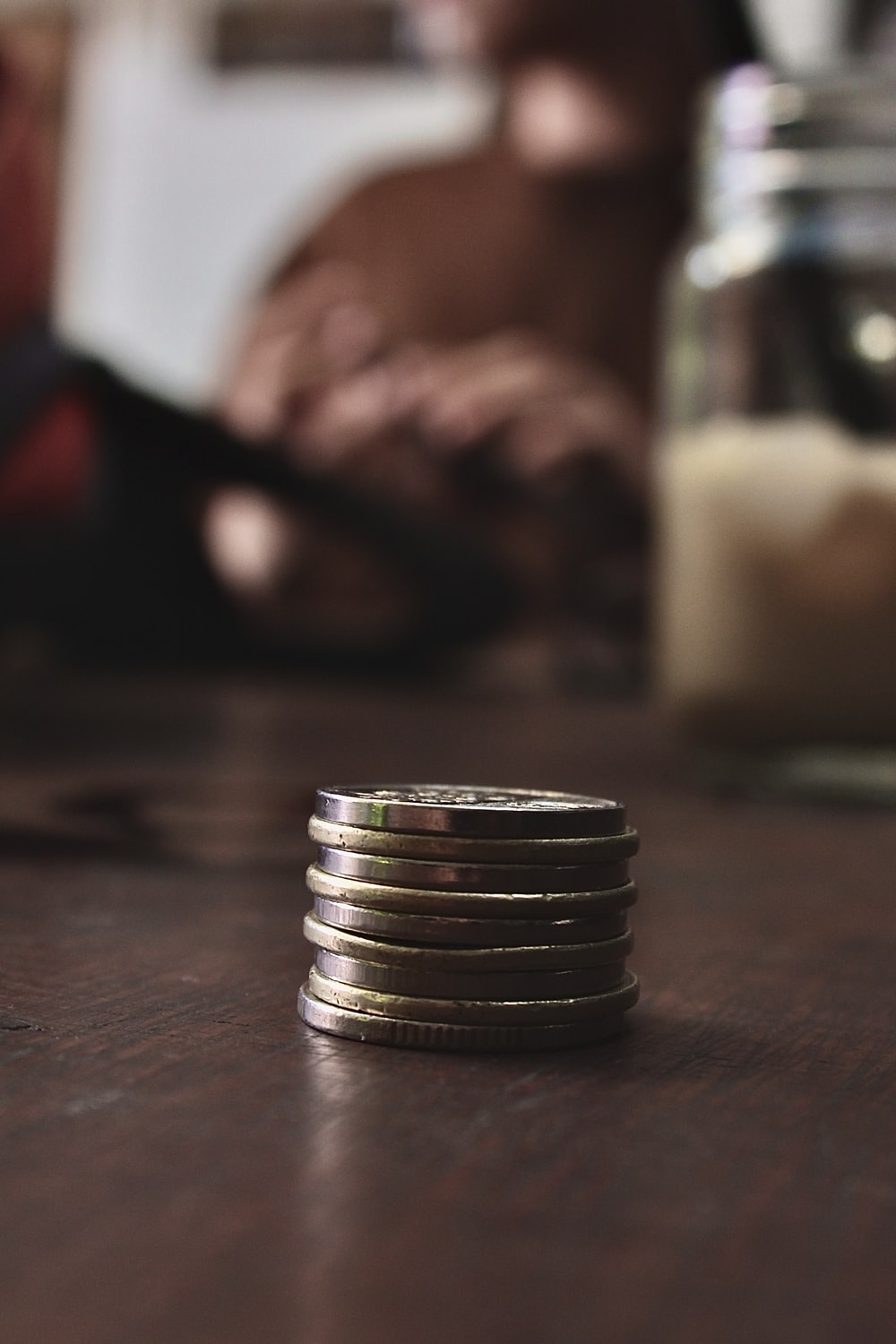 silver and gold round coins on brown wooden table