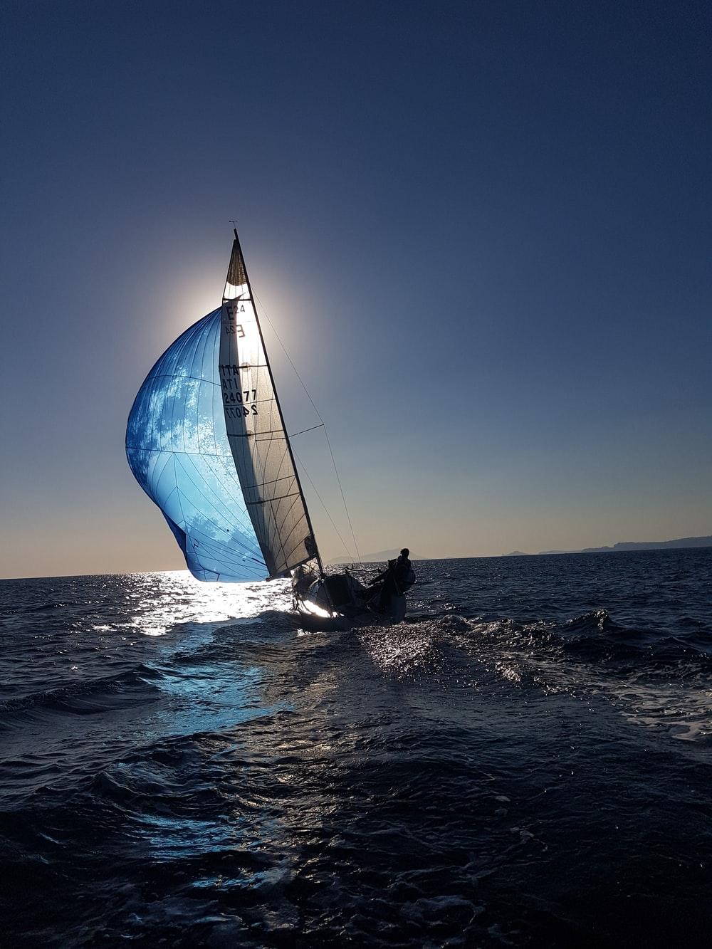 people riding on sailboat on sea during daytime