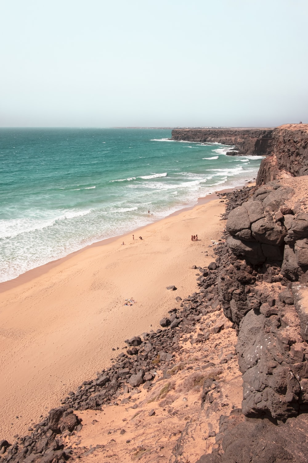 brown sand beach with brown sand and blue sea water during daytime