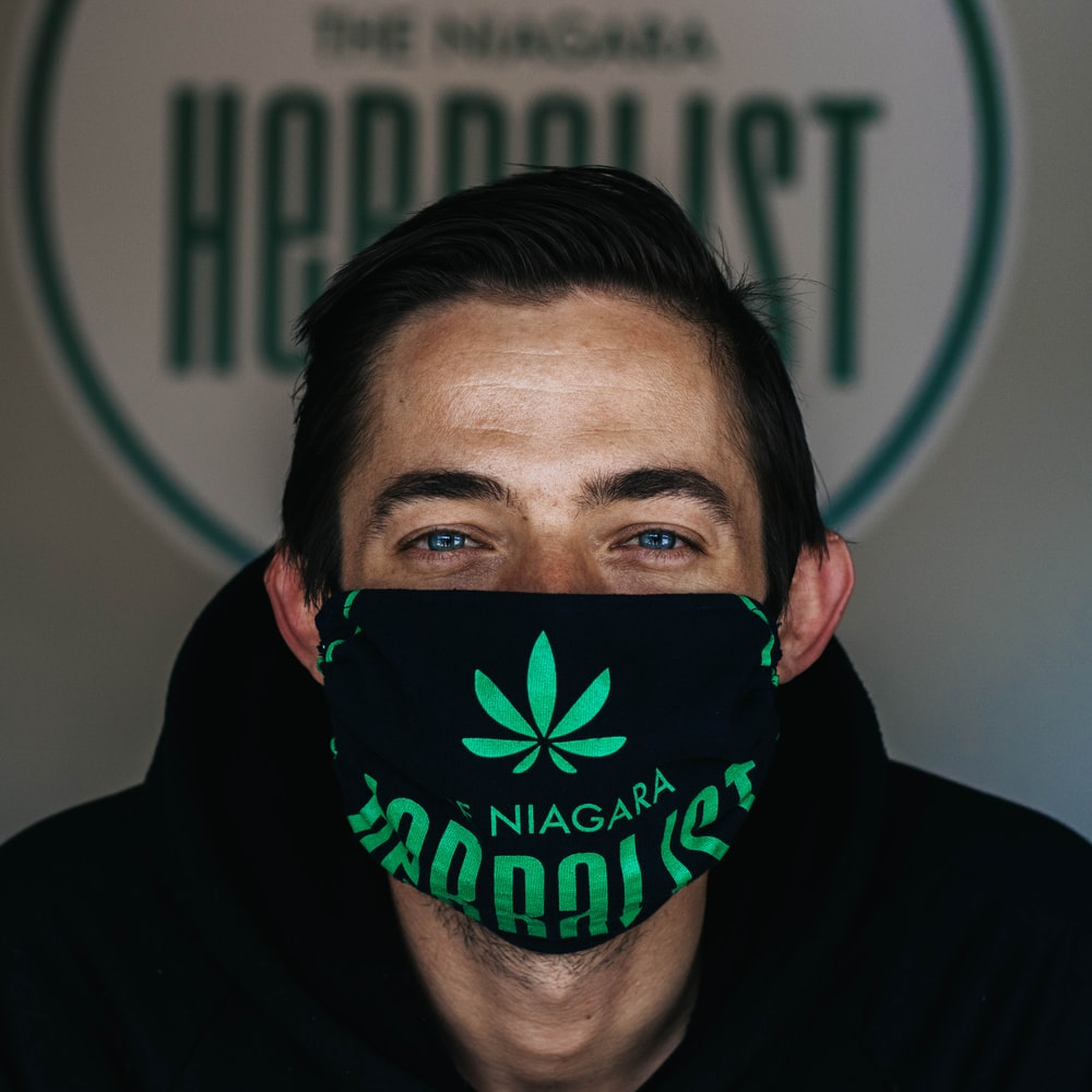 man in black hoodie with green and black mask