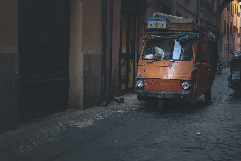 orange volkswagen t-2 parked beside brown concrete building during daytime