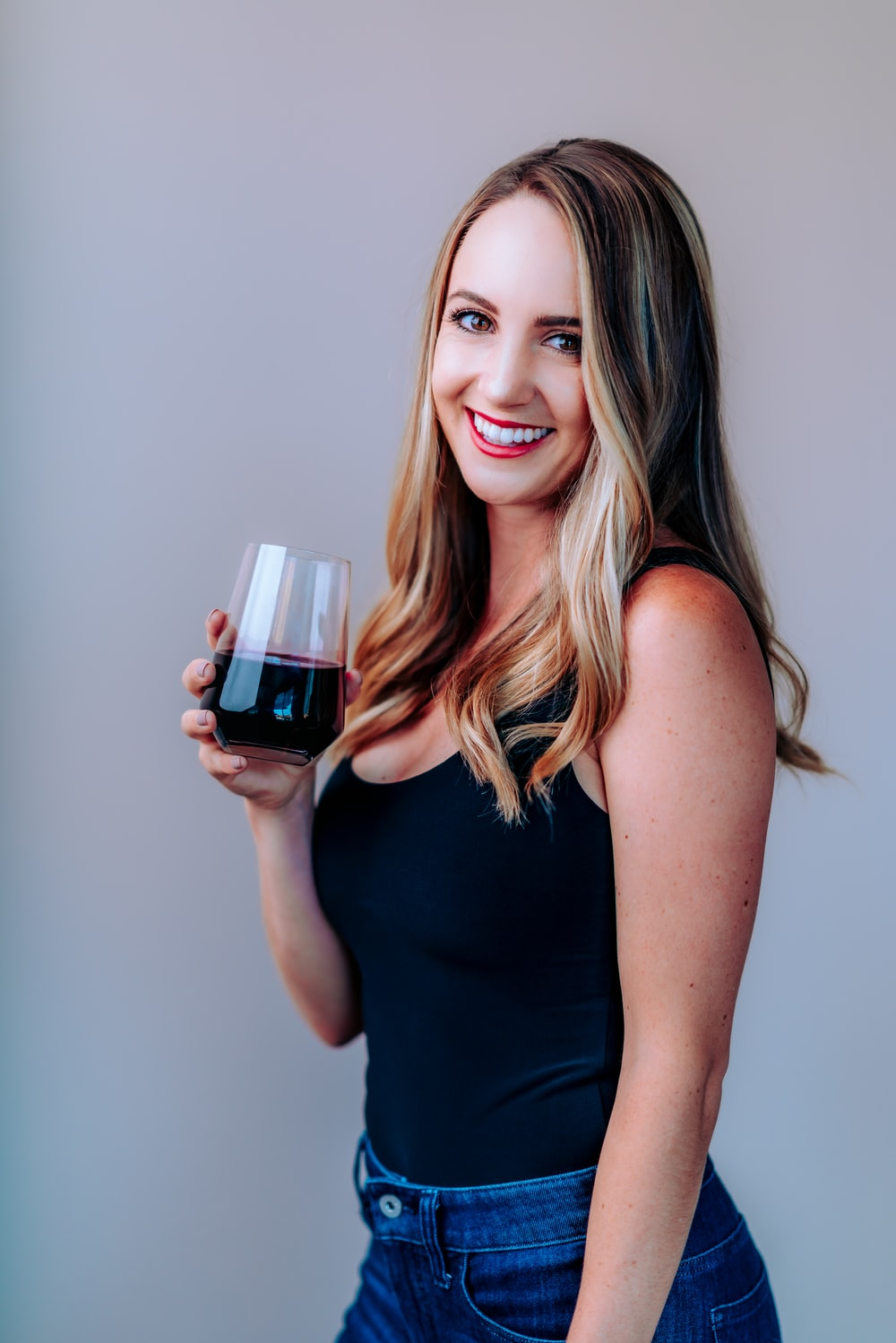 woman in black tank top holding wine glass