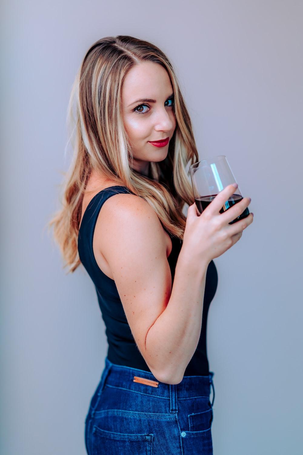 woman in blue tank top holding white ceramic mug