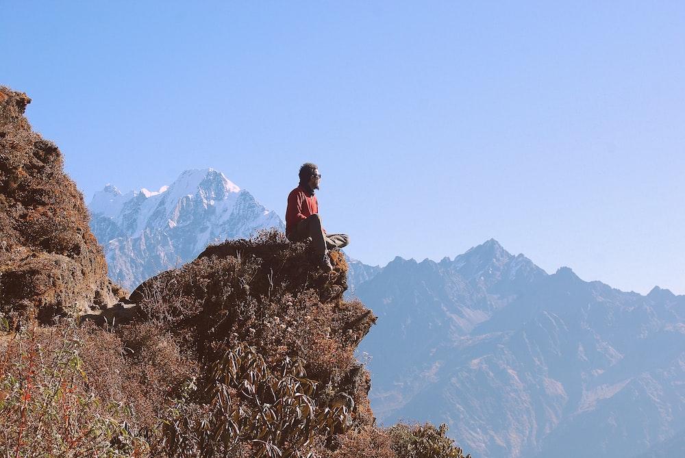man in black jacket sitting on rock mountain during daytime