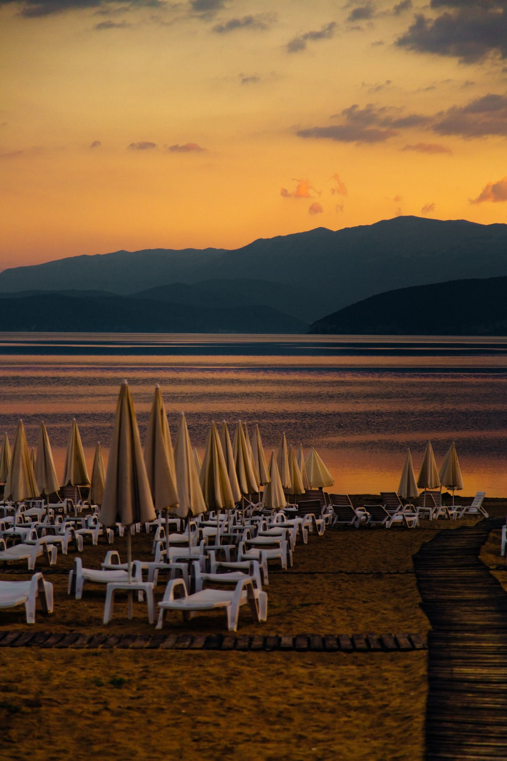 white chairs on beach during sunset