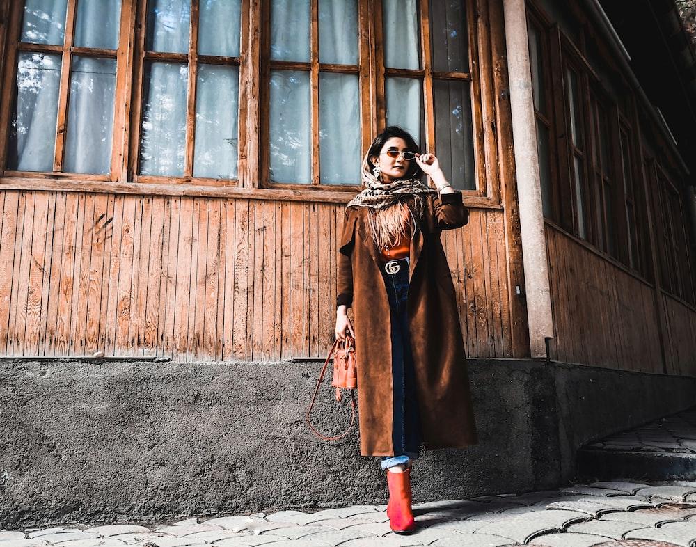 woman in brown coat standing in front of brown wooden door