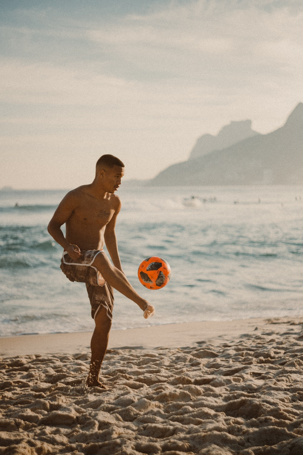 man in red shorts holding yellow and red balloons on beach during daytime