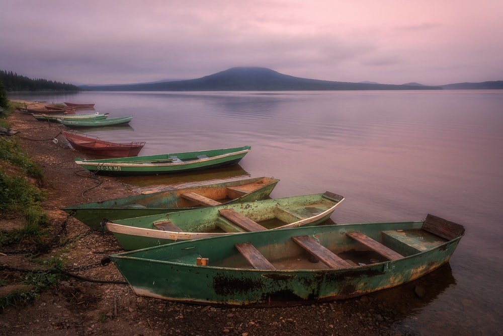 green and brown wooden boat on shore during daytime
