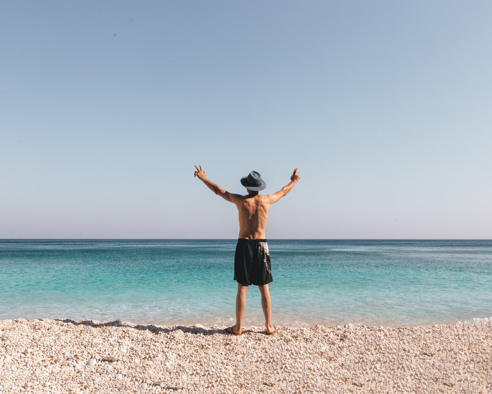 man in black shorts standing on beach during daytime