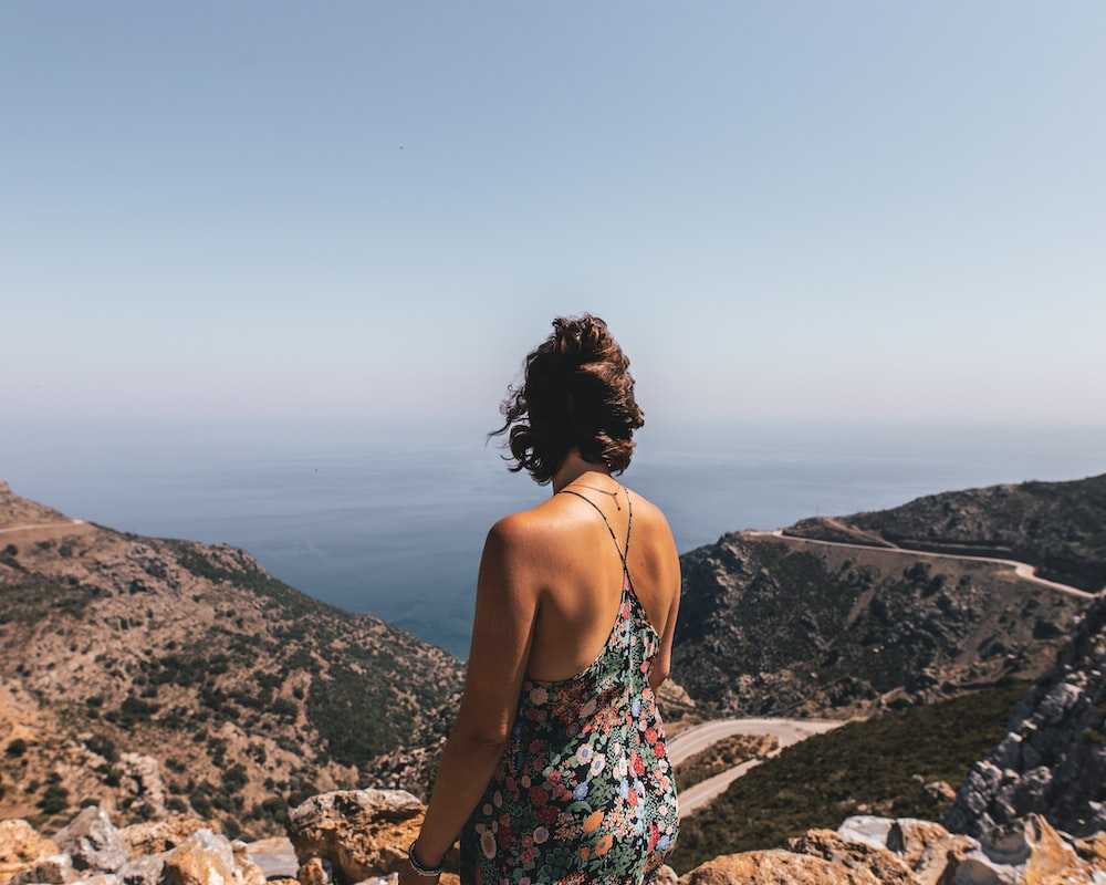woman in white red and blue floral spaghetti strap top standing on brown rock formation during