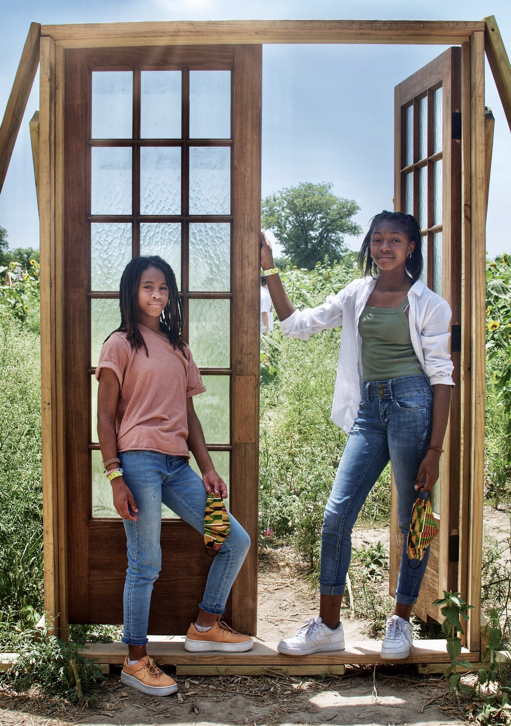 2 women standing beside brown wooden framed glass window during daytime