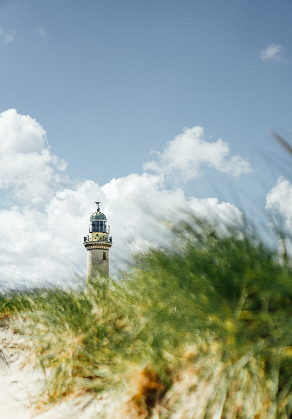white and black lighthouse under white clouds and blue sky during daytime