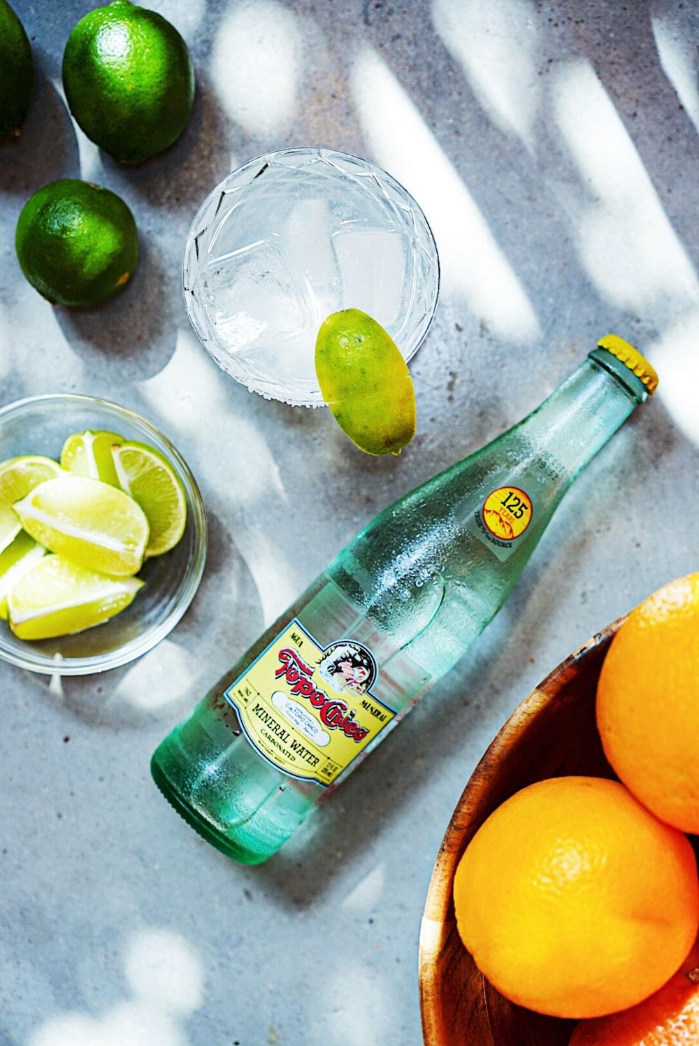 green glass bottle beside orange citrus fruit