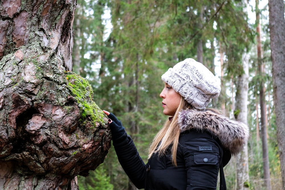 woman in black jacket and white and brown knit cap standing on brown tree trunk during