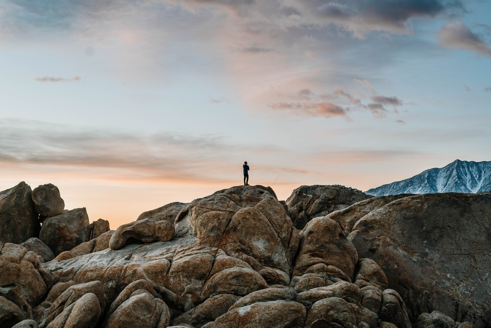 person standing on brown rock formation under white clouds during daytime