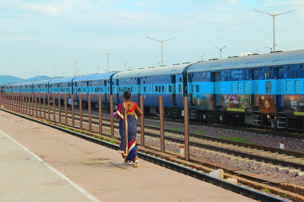 man in blue and white striped shirt standing beside blue train during daytime