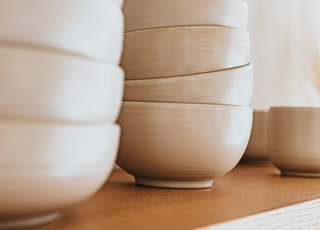 white ceramic bowls on brown wooden table