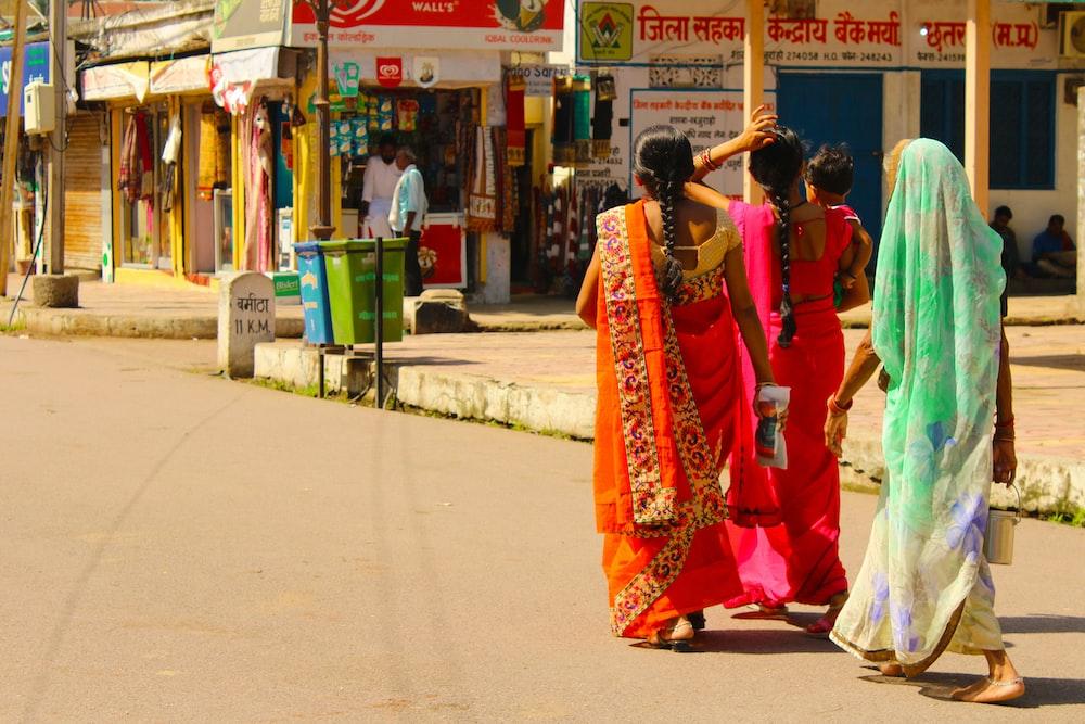 woman in red and white sari dress walking on sidewalk during daytime