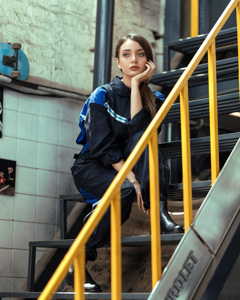 woman in blue and black jacket standing beside yellow metal railings