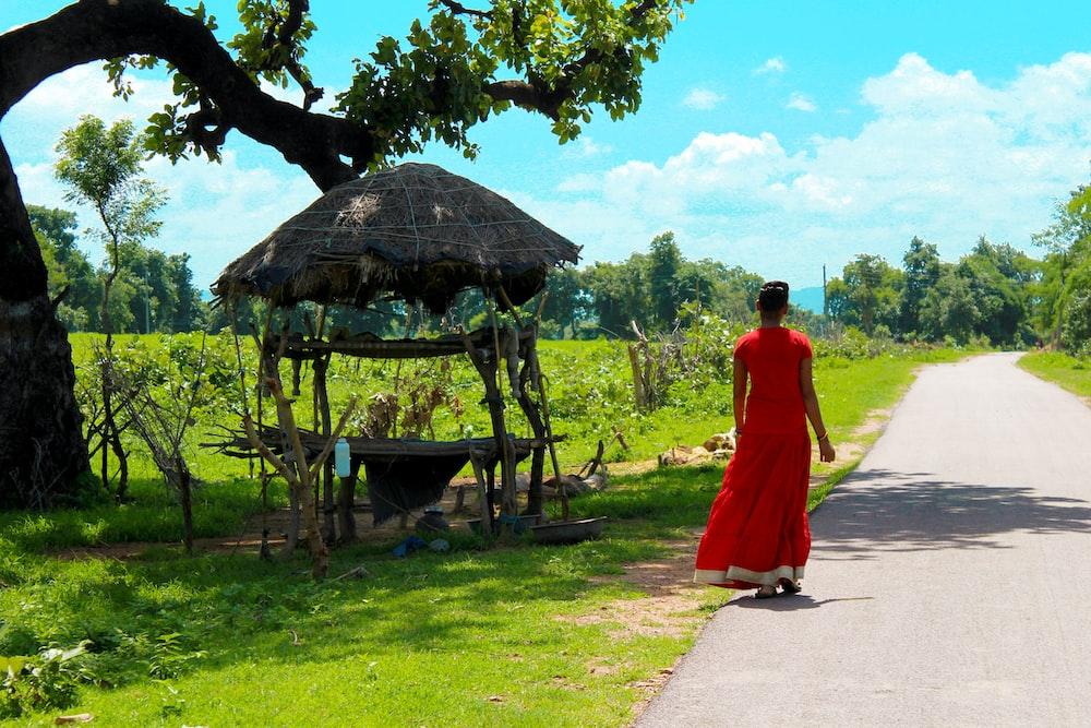 woman in red dress walking on pathway near brown wooden gazebo during daytime