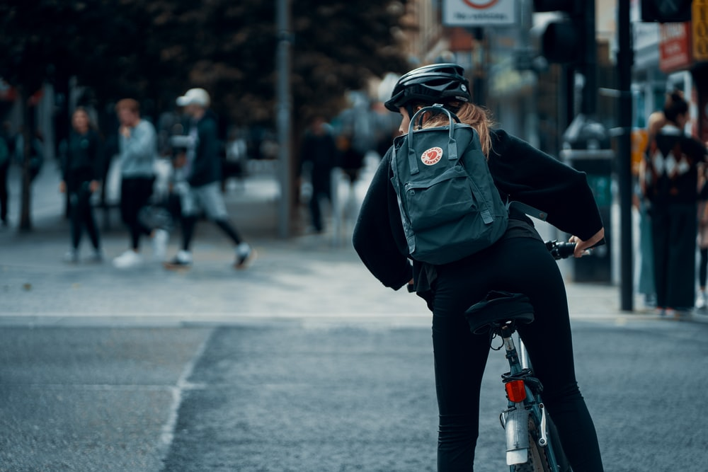 person in black jacket and black pants with green backpack riding on black motorcycle during daytime