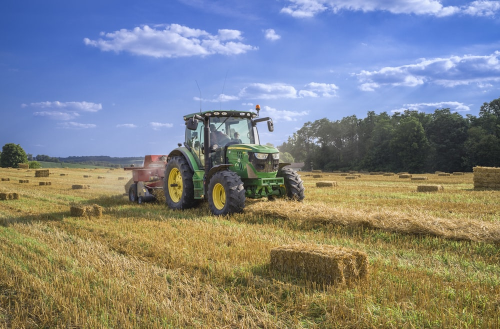 green tractor on brown grass field under blue sky during daytime