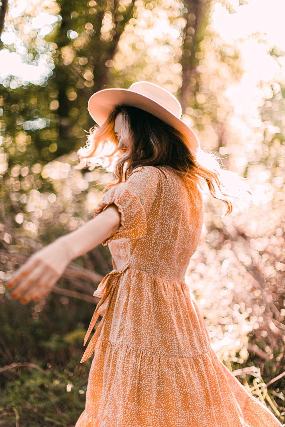 woman in brown and white dress wearing brown hat standing near white flowers during daytime