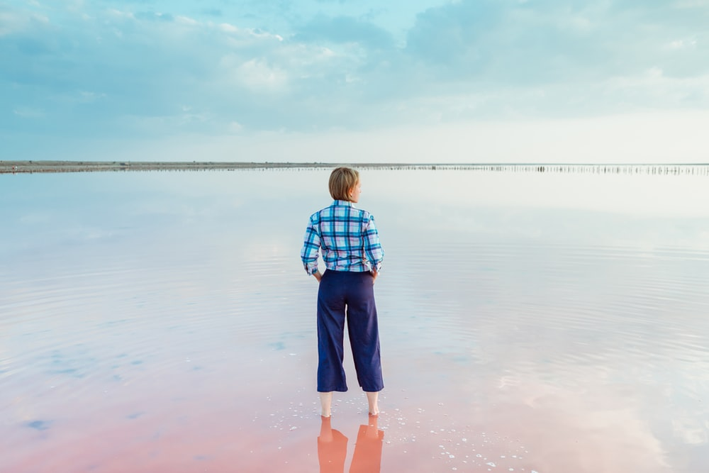 boy in blue and white plaid shirt and blue shorts standing on water during daytime