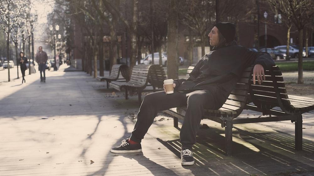 man in black jacket sitting on bench