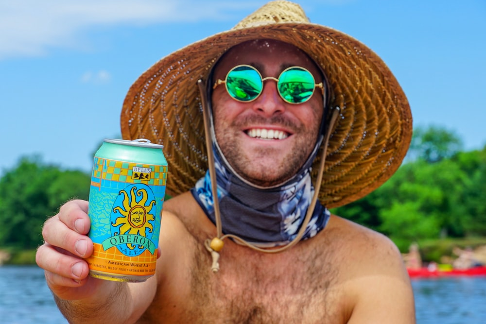 topless man wearing brown straw hat holding yellow and blue can