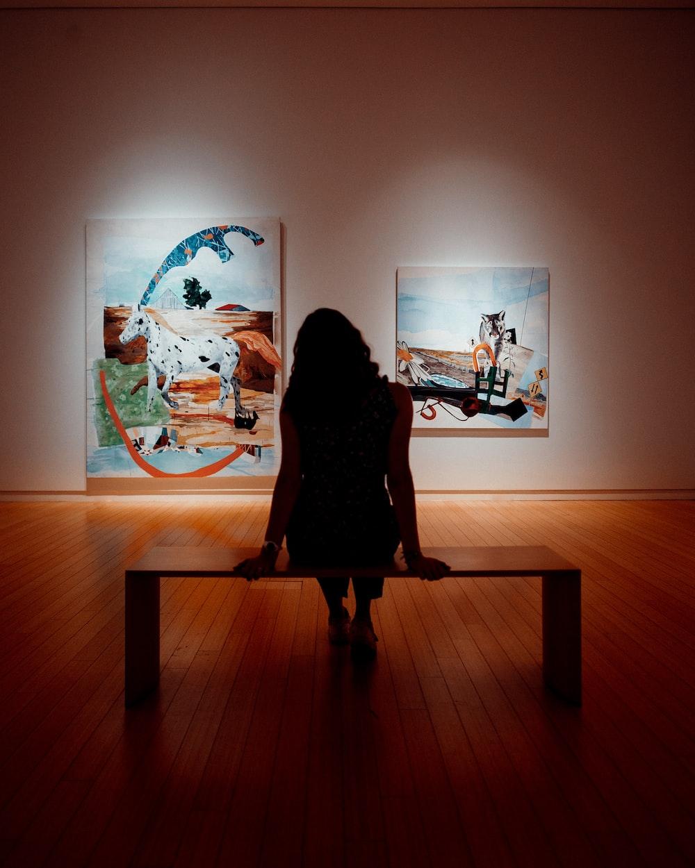woman in black dress standing on brown wooden floor