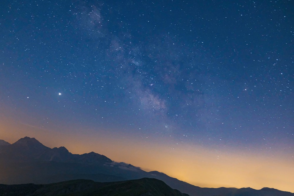 silhouette of mountains under blue sky with stars during night time