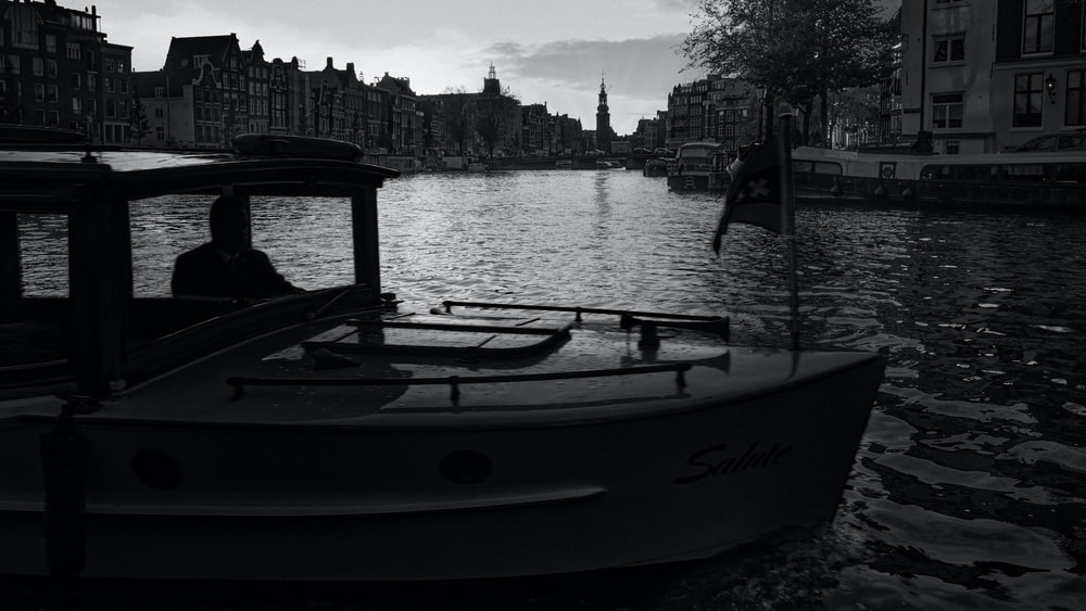 grayscale photo of boat on river