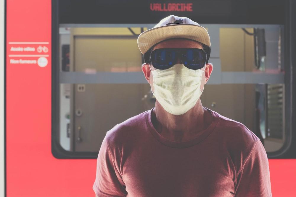 man in red crew neck shirt wearing white mask