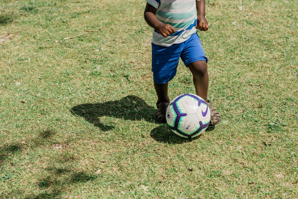 man in white t-shirt and blue shorts playing soccer during daytime