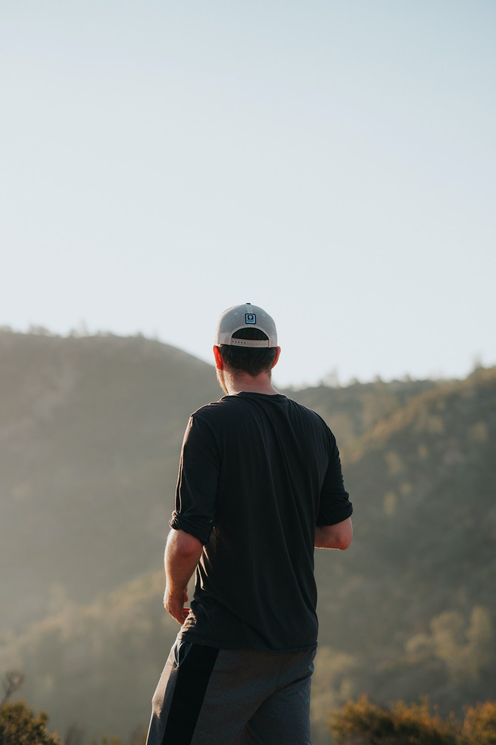 man in black crew neck t-shirt and white cap standing on mountain during daytime