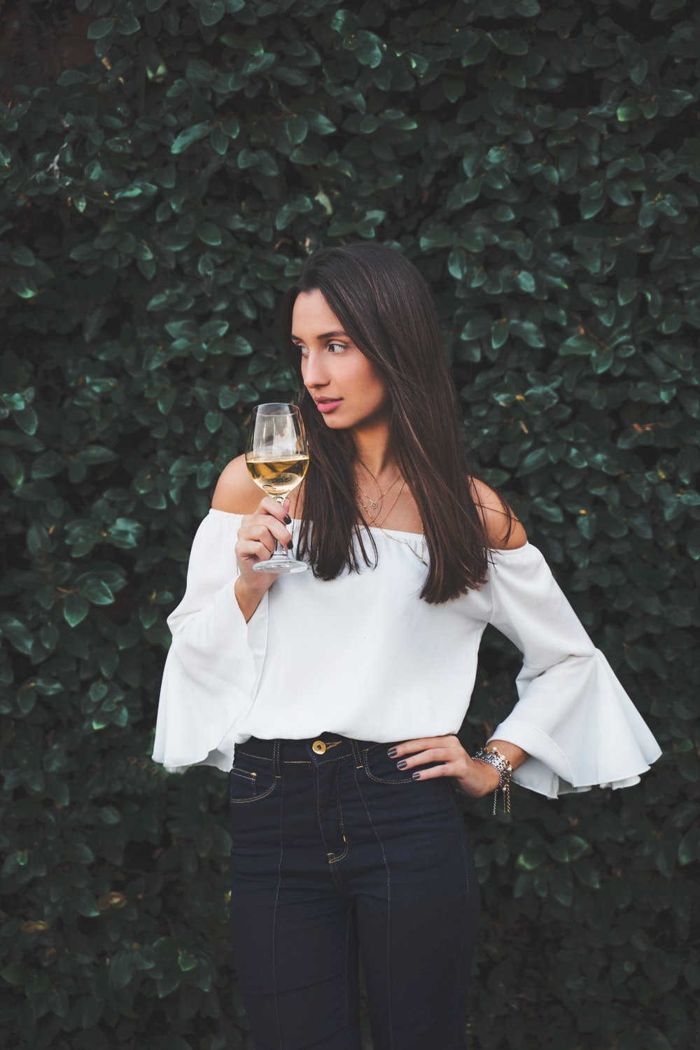 woman in white long sleeve shirt holding clear drinking glass