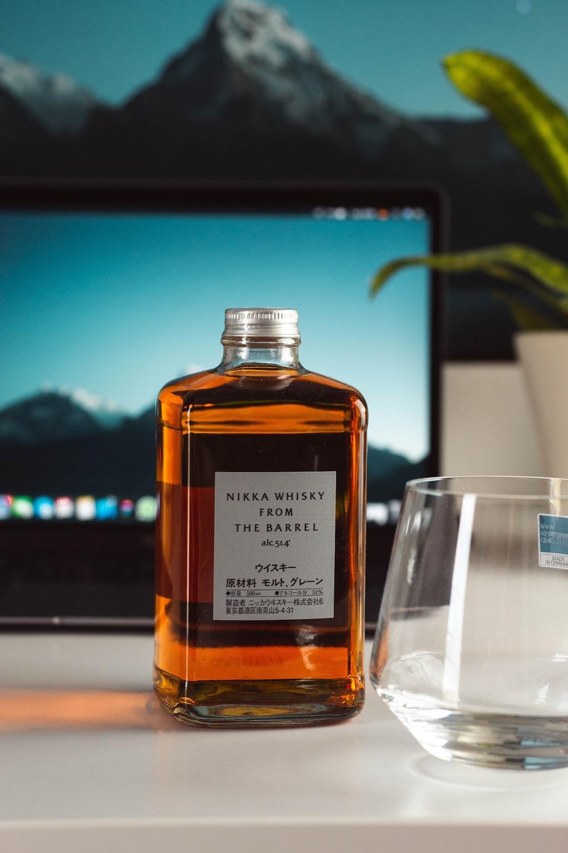 brown glass bottle beside clear drinking glass