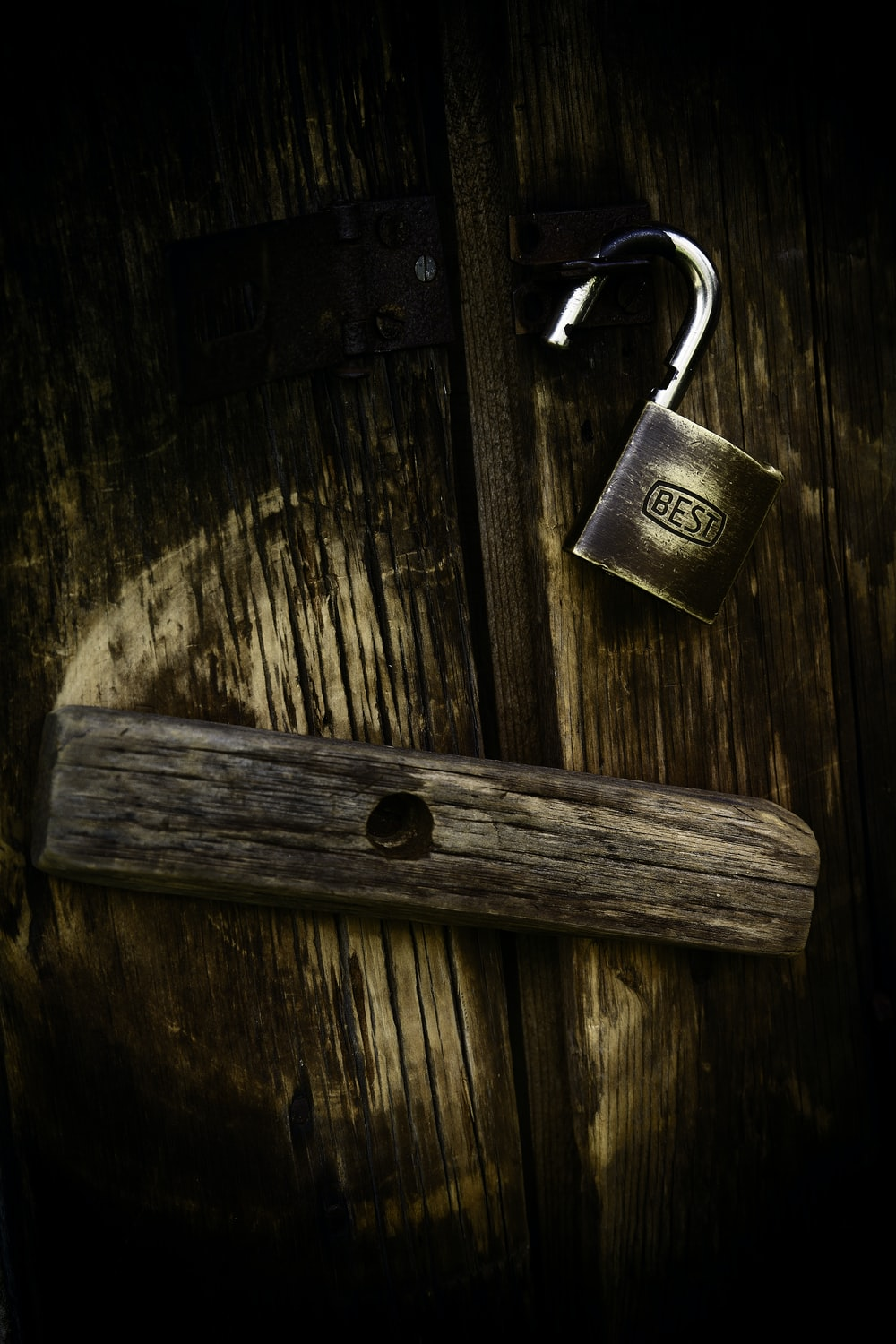 gold padlock on brown wooden surface