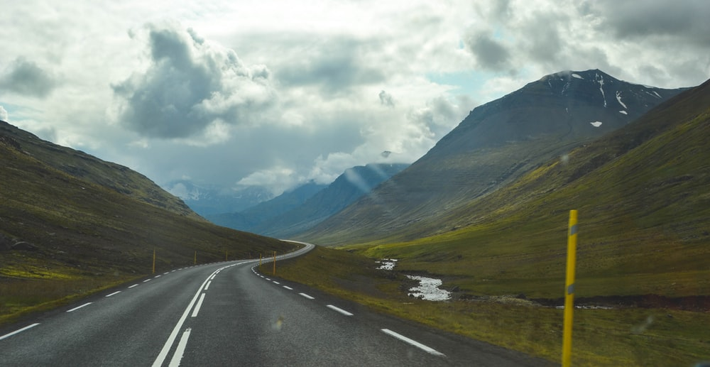 gray asphalt road near green mountains under white clouds during daytime