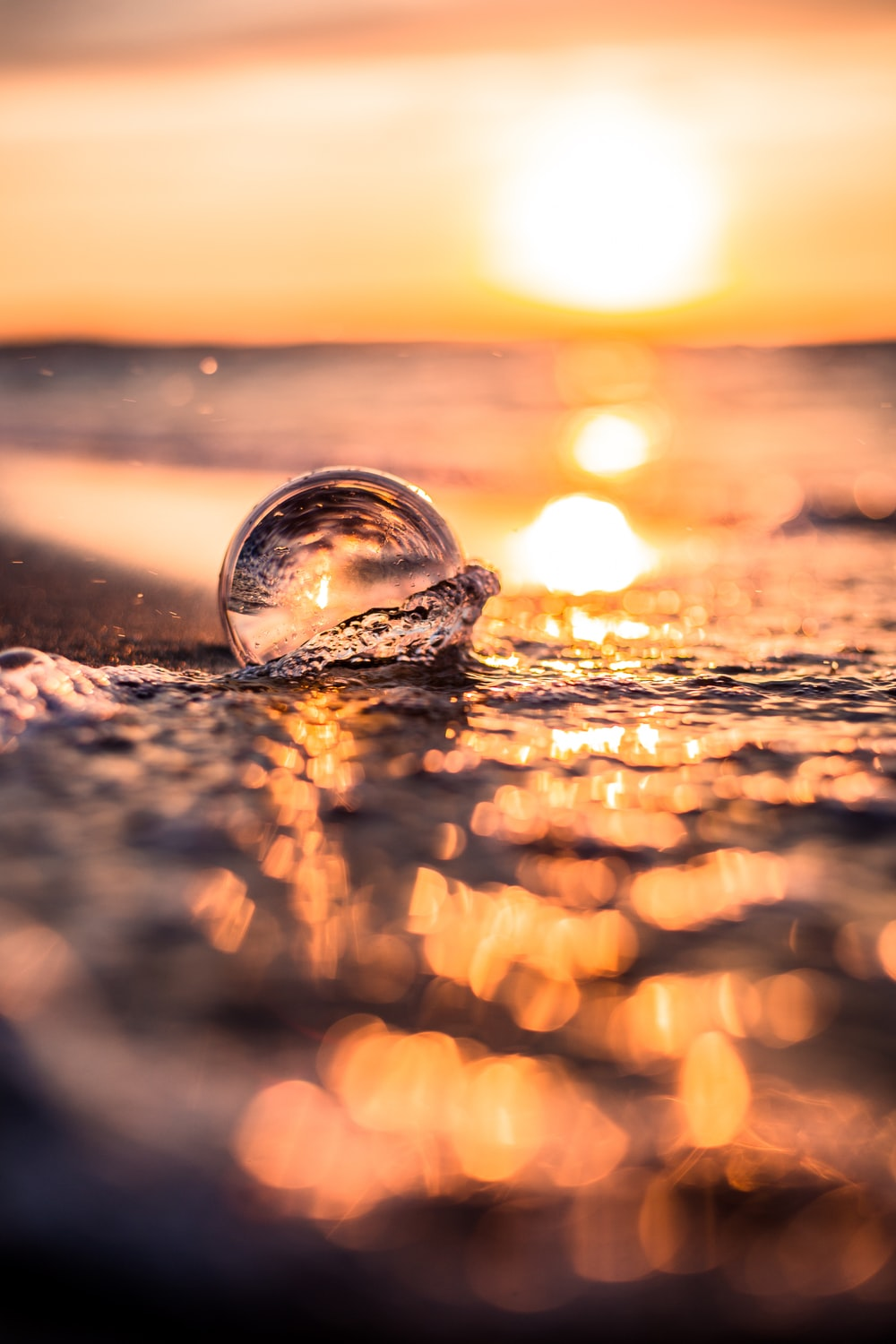clear glass ball on beach during sunset