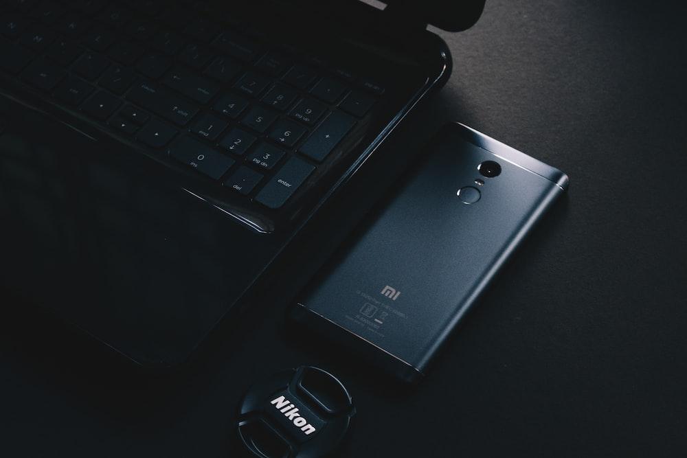 black lg android smartphone on black laptop computer