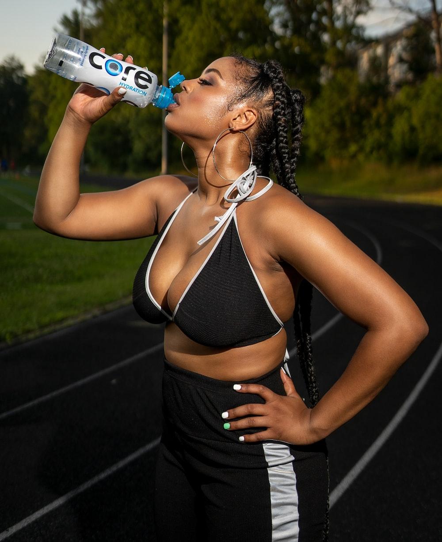 woman in black bikini drinking pepsi can