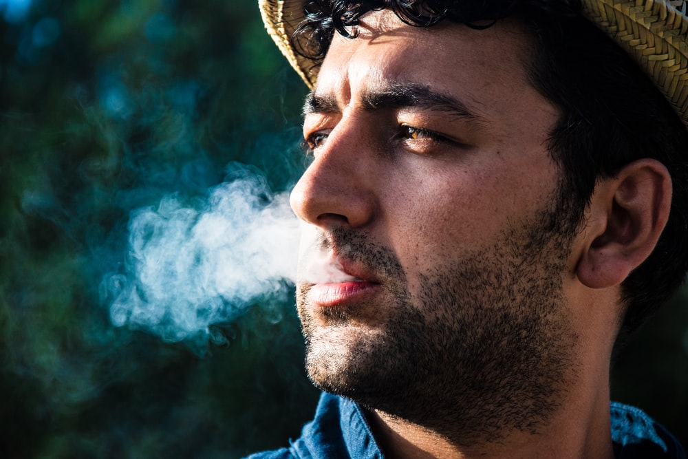 man in blue shirt with white smoke in his face