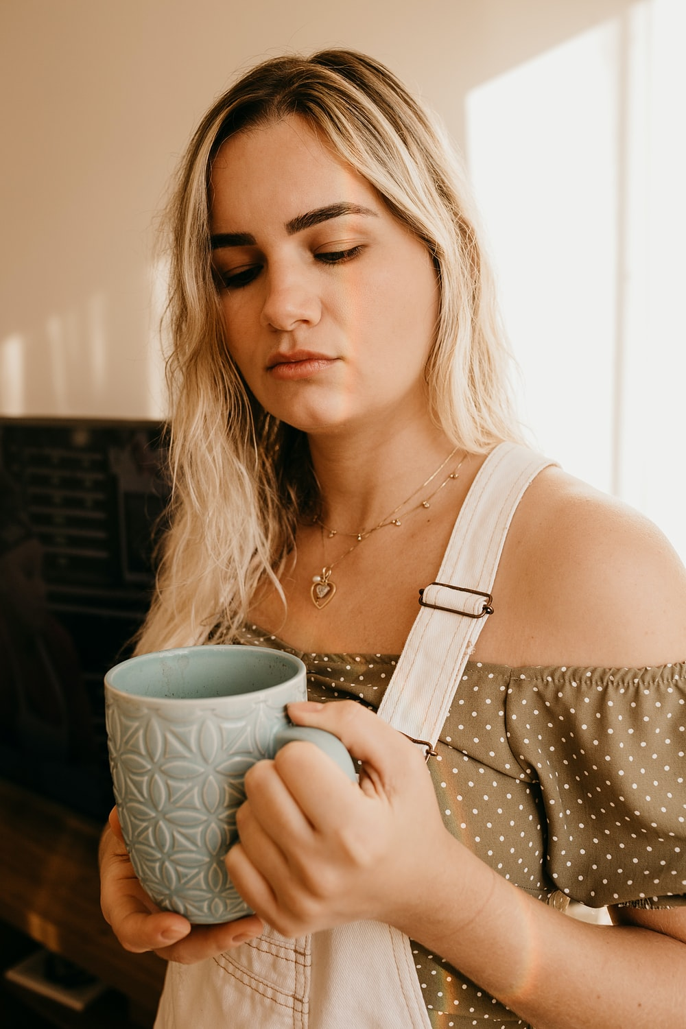 woman in white tank top holding white and green ceramic mug