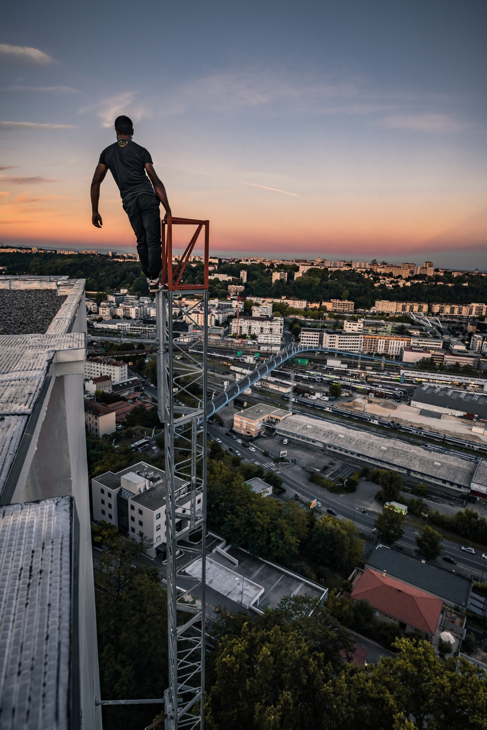 man in black jacket and pants standing on top of building during sunset