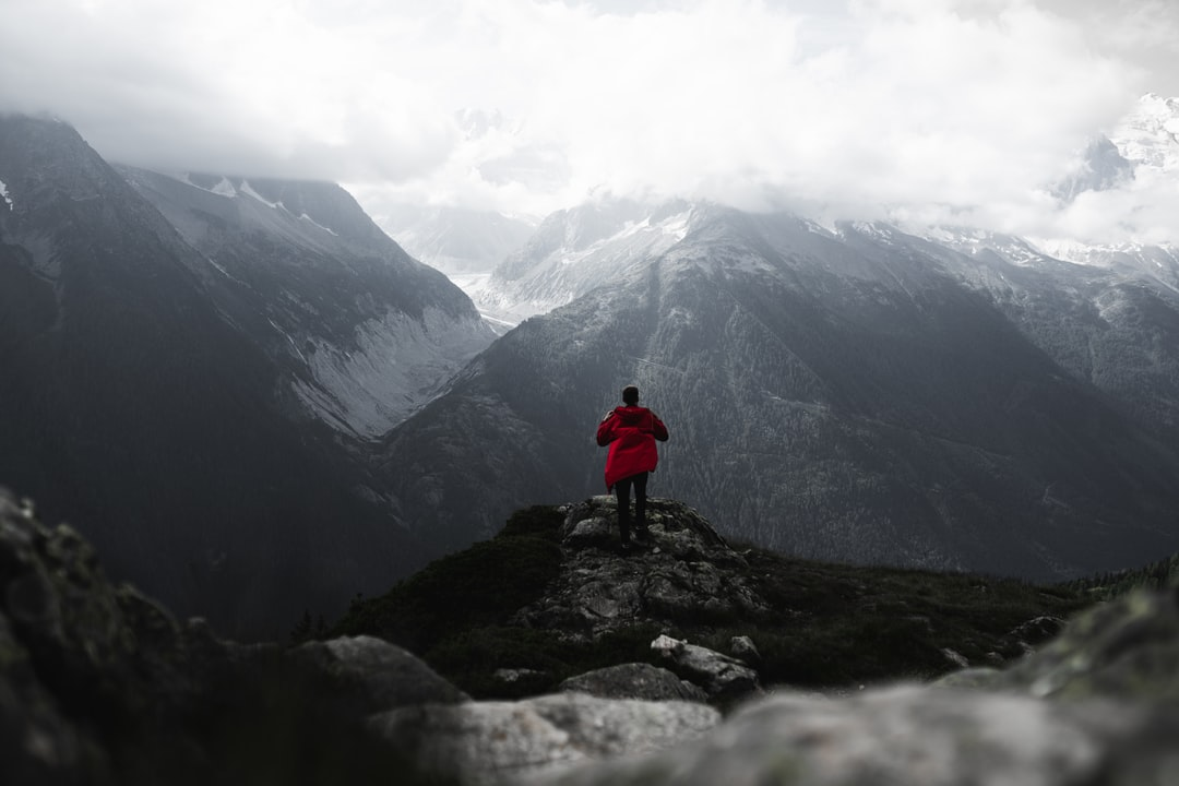 Man standing on a cliff wearing a red rain coat in the French Alps - Luca Massimilian