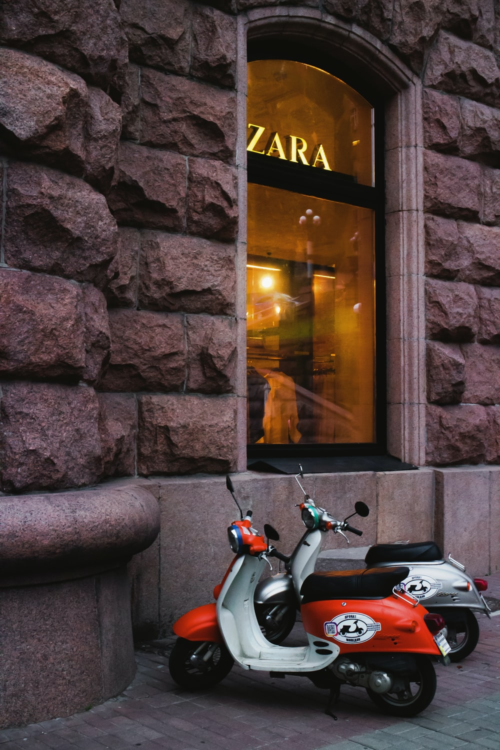 red and black motor scooter parked beside brown brick wall