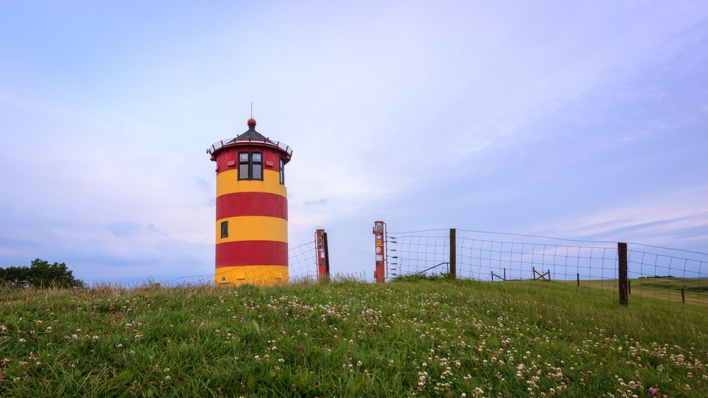 red and brown lighthouse on green grass field under white clouds during daytime